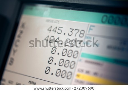 CNC machine monitor display with program code running and numbers with parameters changing  - stock photo