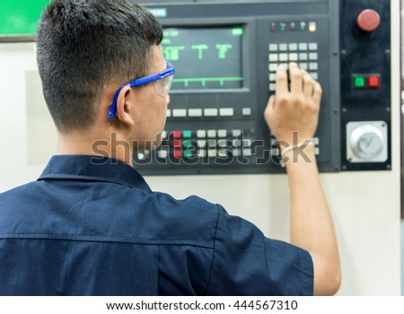 CNC operator, mechanical technician worker at metal machining milling center in tool workshop inserting data with keyboard wearing
