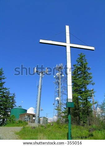 Co-existence of A mountaintop monument to religion and communication towers surrounded by barb wire and chain link fence