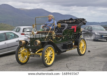 CO. KERRY, IRELAND - JULY 11 2006: The proud owner of an elegant vintage car from the Edwardian era drives off from a roadside car park in the Kerry mountains.