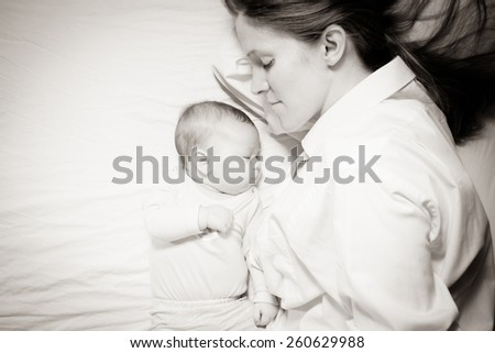 co-sleeping mother and three months baby after breastfeeding on the bed - stock photo