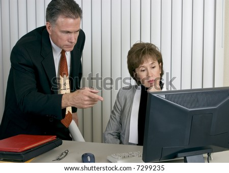 Co-workers discussing or analyzing something on a computer monitor. - stock photo