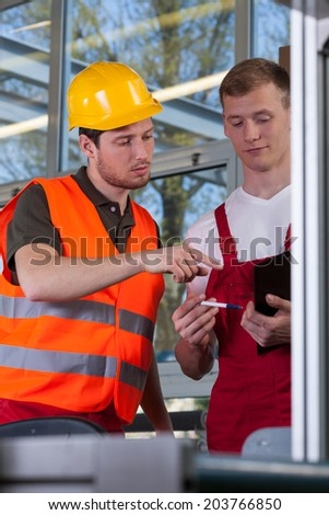 Co-workers during work in a factory, vertical - stock photo