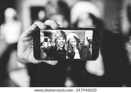 Co-workers goofing around and taking selfies at their modern office, New Year selfie. Black and white - stock photo