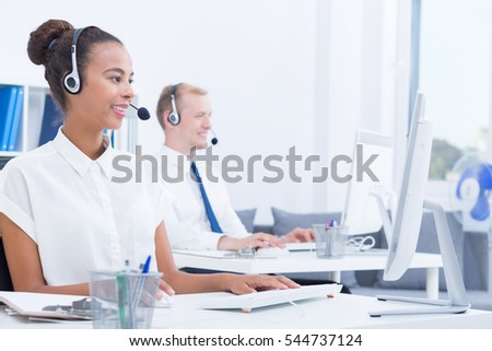 Co-workers in telemarketing office are sitting in front of computers