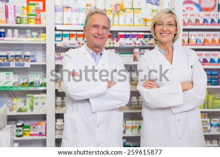 Co-workers smiling at camera with arms crossed in the pharmacy