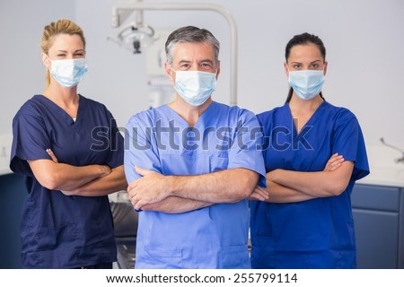 Co-workers wearing surgical mask with arms crossed in dental clinic - stock photo