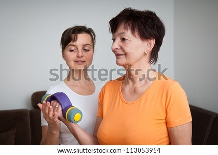 Coach assisting senior woman exercising with barbells - stock photo