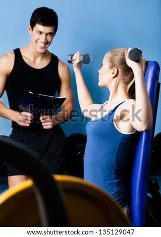 Coach controls sports actions of pretty woman working out with dumbbells in gym