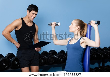 Coach controls sports actions of pretty woman working out with dumbbells in gym class