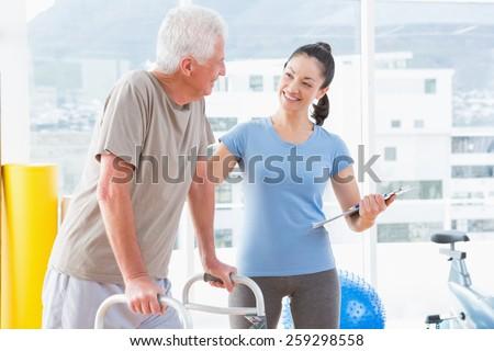 Coach encouraging senior man in fitness studio - stock photo