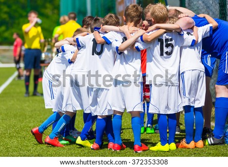 Coach giving young soccer team instructions. Youth soccer team together before final game. Football match for children. Boys group shout team, gathering. Coach briefing. Soccer football background. - stock photo