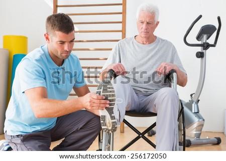 Coach helping invalid senior in fitness studio - stock photo