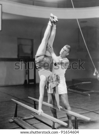 Coach helping woman on parallel bars - stock photo