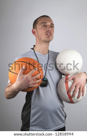 Coach is watching after his boys, holding a lot of balls. - stock photo