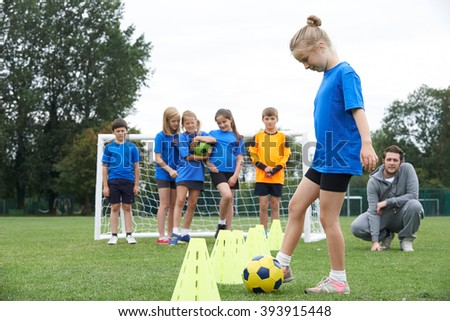 Coach Leading Outdoor Soccer Training Session - stock photo