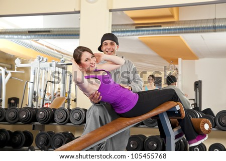 coach motivating young woman doing abdominal muscle exercises in gym - stock photo