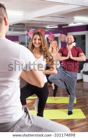 Coach showing to adult learners new yoga posture inside - stock photo