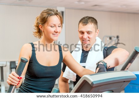 Coach shows the girl working of equipment in the gym - stock photo