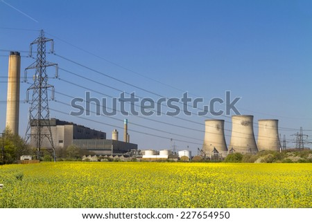 Coal fired power station viewed across a field of yellow rapeseed flowers - stock photo