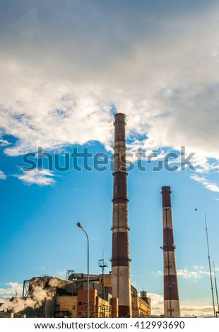 Coal Fossil Fuel Power Plant with Smokestacks, energy plant in sunset light.