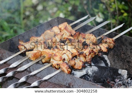 Coal grill of pork skewers with tomatoes, onion and peppers. barbecue camping dinner. - stock photo