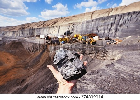 Coal mine - coal on the palm - stock photo