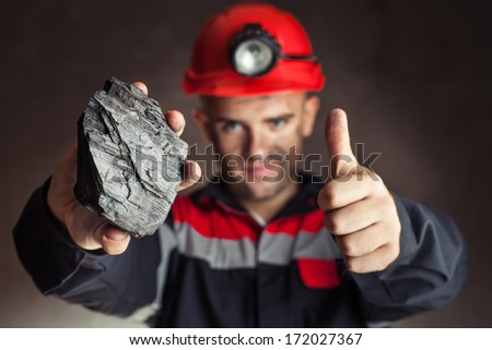 Coal miner showing lump of coal with thumbs up against a dark background