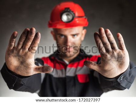 Coal miner with dirty hands making stop gesture warning of danger against a dark background