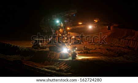 Coal mining in an open pit with huge industrial machine at night shoot - stock photo