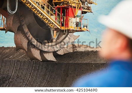 Coal mining in an open pit - Worker is looking on the huge excavator - industry in Czech Republic