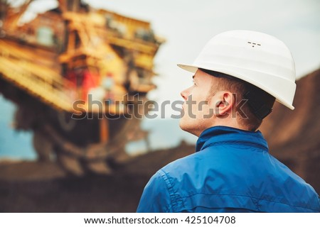 Coal mining in an open pit - Worker is looking on the huge excavator - industry in Czech Republic - stock photo