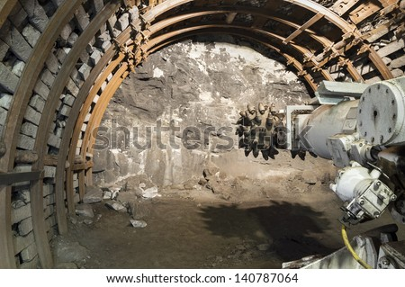 Coal mining mechine with rotating cutting drum - stock photo