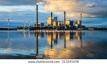 Coal power plant at water front with reflection - stock photo
