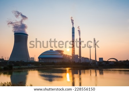 coal power station with the setting sun , industrial landscape  - stock photo