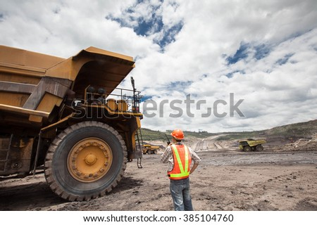 Coal trucks and loaders are hauling the coal away to to a power plant simultaneously. - stock photo