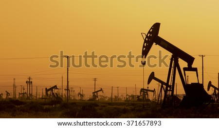Coalinga, California USA - April 29, 2011:  Pumpjacks under amber sky in late afternoon at the  Guijarral Hills oil fields