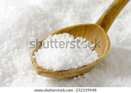 coarse grained sea salt with the wooden teaspoon - stock photo