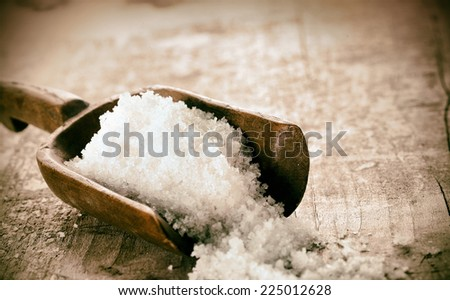 Coarse granules of natural rock or sea salt in a rustic old wooden ladle spilling out onto a grunge wooden table - stock photo