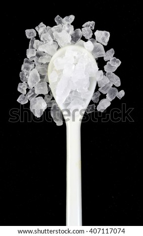 Coarse rock salt in a white spoon isolated  on a black background - stock photo