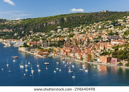 Coast aerial view of scenic French Riviera town Villefranche-sur-Mer with leisure boats anchored in harbor, citadel and fort Mont Alban on hill. - stock photo