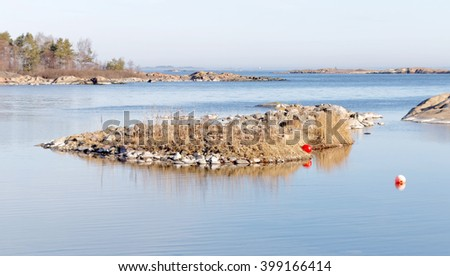 Coast, cliffs, islet and ocean a sunny day during spring time in scandinavia - stock photo