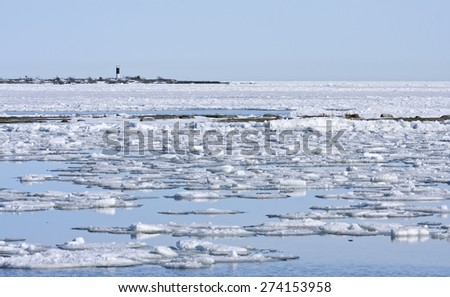 Coast, coastline and shore of the Baltic Sea in March during the day, hours when the ice at sea breaks up. Sunny day by the sea. Lighthouse, beacon in the background. - stock photo