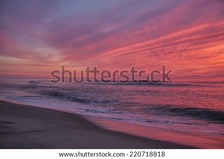 Coast Guard beach with color sky just before sunrise.  Ocean waves forming near shore.  Eastham MA, Cape Cod - stock photo