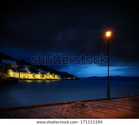 Coast, illuminated village next to harbor at night, with rope and lantern on jetty - stock photo