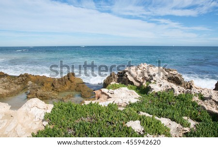 Coast line at Penguin Island with limestone, plants and turquoise Indian Ocean seascape in Rockingham, Western Australia/Turquoise Seascape with Limestone/Penguin Island, Rockingham, Western Australia - stock photo