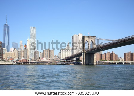 Coast Manhattan with lots of skyscrapers and a pier with Brooklyn Bridge - stock photo