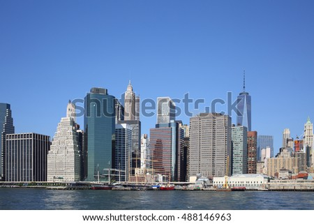 Coast Manhattan with lots of skyscrapers and a pier with sailing ships