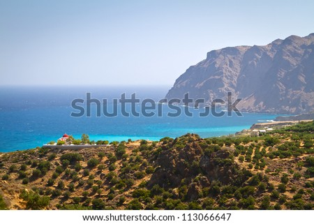Coast of Crete with olive trees and traditional Greek church