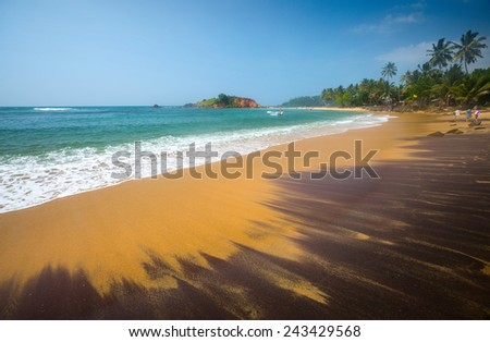 Coast of Indian Ocean near the town of Mirissa with mix of black and yellow sand. Sri Lanka. - stock photo